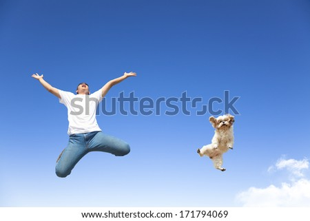young man and dog jumping in the sky - stock photo