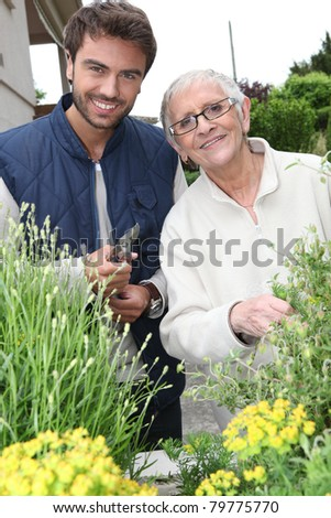 Young man and elderly woman gardening - stock photo