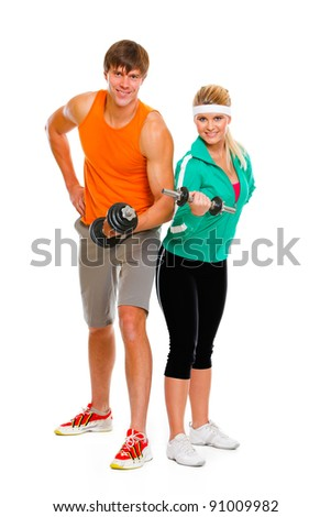 Young man and fit woman lifting a dumbbell isolated on white