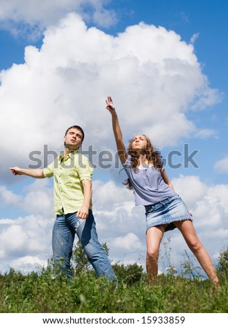 Young man and girl dancing on green grass against sky