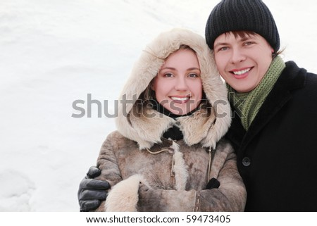 young man and girl in warm dress smiling, embracing and looking at camera, half body, winter day
