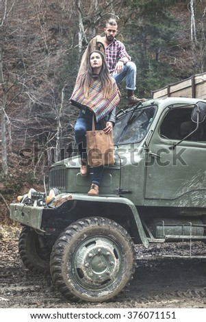 Young man and girl on truck with logs in the forest
