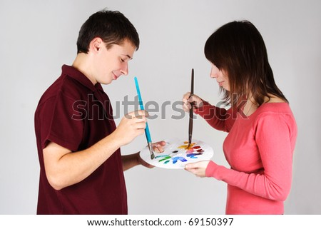 young man and girl standing and mixing paint on palette - stock photo