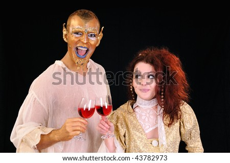 Young man and girl toasting with artistic painted faces - stock photo