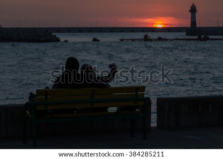young man and girl watching a romantic sunset.
