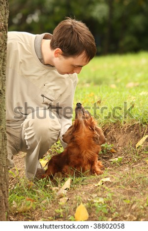 Young man and his adorable dachshund  outdoor looks on each other