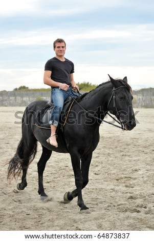 young man and his black stallion on the beach