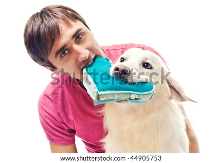 Young man and his dog fighting over a heart shaped pillow - stock photo