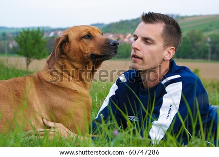 Young man and his dog in nature - stock photo