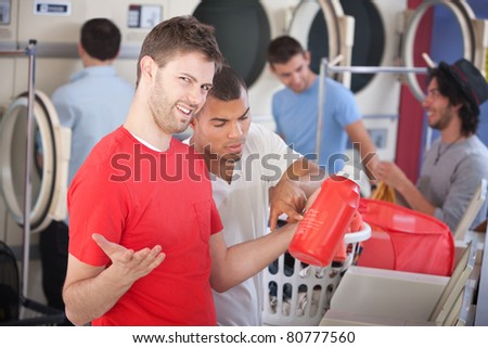 Young man and his friend struggle with soap instructions in the laundromat - stock photo