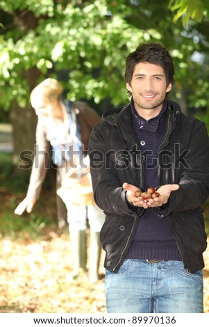 Young man and his girlfriend, gathering chestnuts