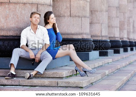 Young man and his girlfriend sit on base of the column in a relaxed poses and smile - stock photo