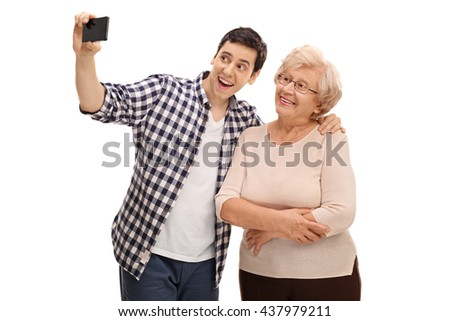 Young man and his grandmother taking selfie with cell phone isolated on white background - stock photo