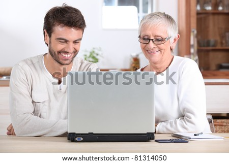 Young man and his mother using laptop - stock photo
