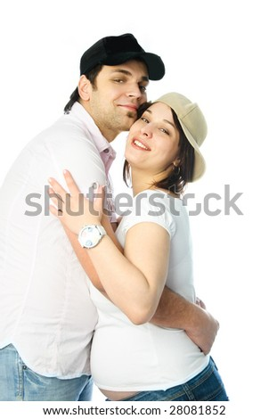 young man and his pregnant wife embracing - stock photo