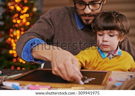 Young man and his son drawing xmas tree on blackboard with chalk