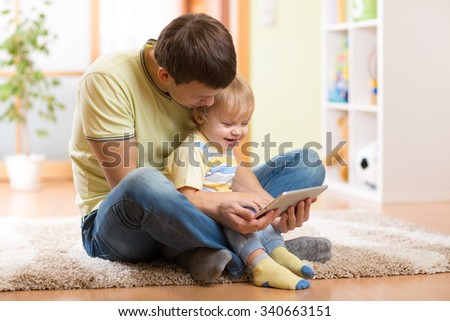 Young man and his son kid playing with tablet computer indoors - stock photo