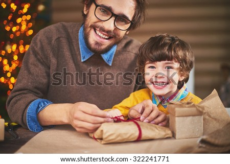 Young man and his son looking at camera with smiles while packing xmas gifts - stock photo