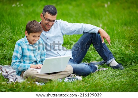 Young man and his son networking outdoors - stock photo