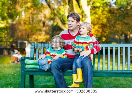 Young man and his two little blond sons sitting together in colorful clothing. Happy kid boys and their dad having fun in autumn park on warm day.