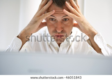 young man and laptop looking stressed - stock photo