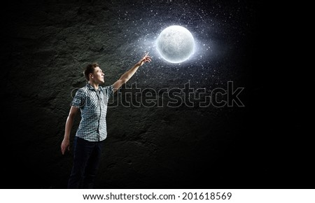 Young man and moon planet against dark background - stock photo