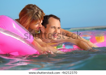 young man and nice women lying on an inflatable mattress in pool - stock photo