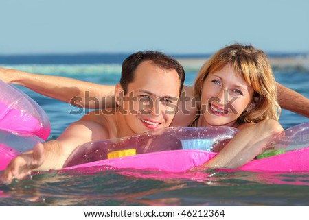 young man and nice women lying on an inflatable mattress in pool, man extended hand forward - stock photo