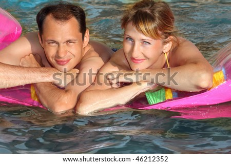 young man and nice women lying on an inflatable mattress in pool, top view - stock photo