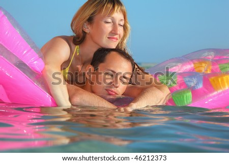 young man and nice women sleep on an inflatable mattress in pool, closed eyes - stock photo