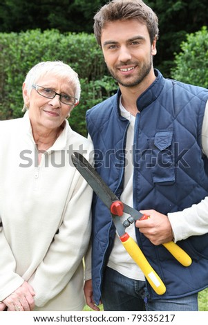 young man and older woman in garden - stock photo