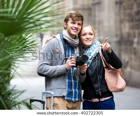 Young man and positive girl with photo camera studying neighborhood