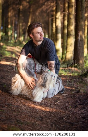 Young man and shih tzu dog portrait at forest. - stock photo