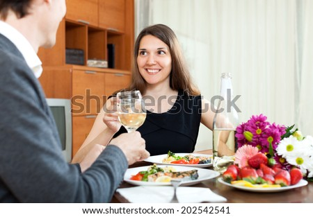 Young man and smiling cute woman having romantic dinner in home - stock photo