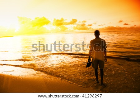 young man and sunset on Caribbean sea - stock photo