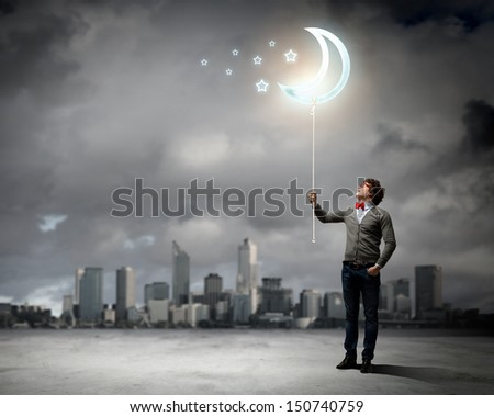 Young man and the moon symbol against polluted and ruined landscape
