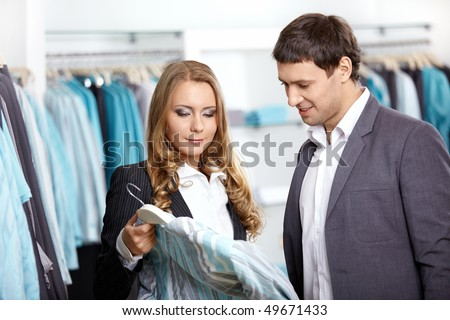 Young man and the woman consider a shirt in shop