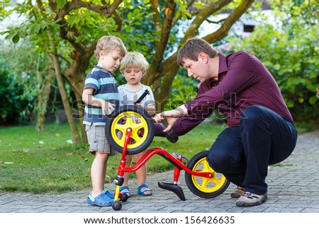 young man and two little sons repairing bicycle outdoors - stock photo