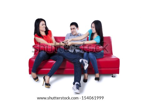 Young man and two woman are fighting for remote control isolated on white background