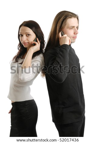 Young man and woman are standing back to back. They are calling by mobile phone at the same time. Happy girl is looking at the camera.