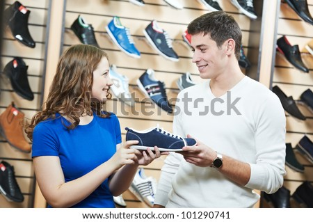 Young man and woman assistant choosing footwear during shopping at shoe shop - stock photo