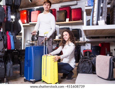 Young man and woman buying travel suitcase in haberdashery shop - stock photo