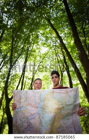 young man and woman checking map during hiking excursion and look for destination. Vertical shape, low angle view