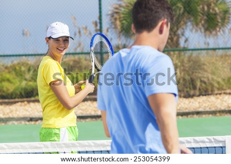 Young man and woman couple playing tennis or having tennis lesson - stock photo