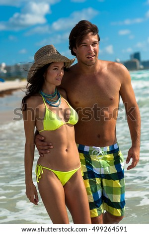 Young man and woman cuddling at beach
