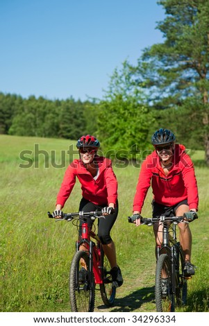 Young man and woman cycling in the nature on a sunny day