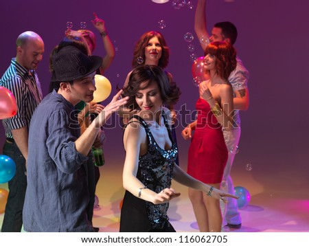 young man and woman dancing and partying, with people on the background, playing with balloons and bubbles - stock photo
