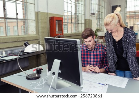 Young Man and Woman Discussing the Reports on Top of Worktable Inside the Office - stock photo