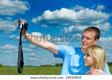 Young man and woman do self-portrait against green field and dark blue sky with clouds - stock photo