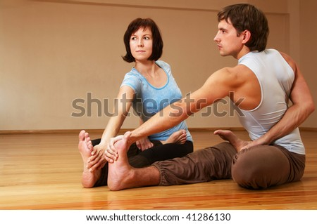 young man and woman doing yoga indoor - stock photo